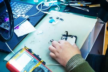 man technician repairing mobile phone