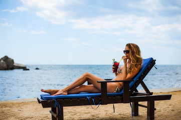 Beautiful bikini woman drink mojito cocktail on a beach