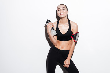 Smiling young fitness woman with armband and bottle of water