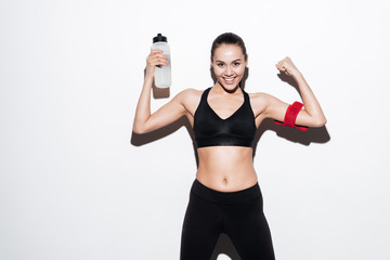 Happy young woman athlete with bottle of water showing biceps