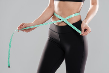 Closeup of fitness woman standing measuring her waist with tape