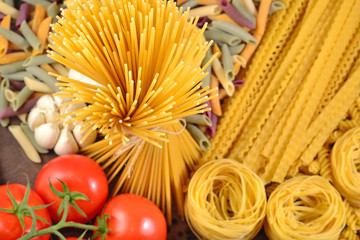 Uncooked Italian pasta, ripe tomatoes branch and garlic