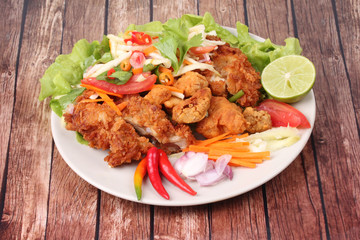 Spicy deep-fried chicken salad with roll green mango .