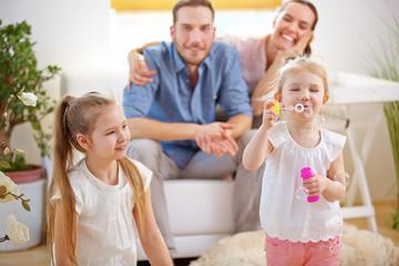 Familie zu Hause beim Seifenblasen pusten