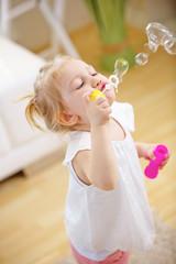 Kleines Kind bläst Seifenblasen zu Hause