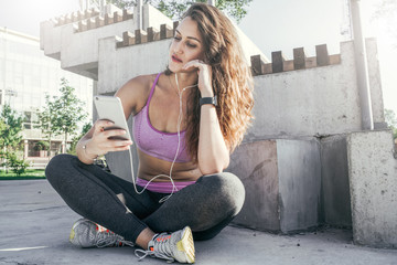 Summer sunny day. Young woman in sports clothing sitting outside on a concrete floor, looking at smartphone screen and listening to music on headphones. Girl uses a gadget, resting after a workout.
