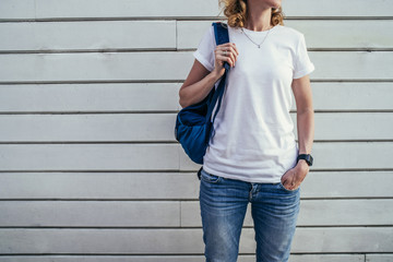 Close-up of young woman with backpack in white T-shirt and blue jeans standing outside with his hand in his pocket. In background white wall of wooden planks. On T-shirt space for text, advertising.