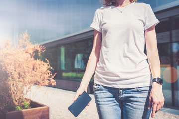 Summer sunny day.Front view,close-up of young woman in white T-shirt and blue jeans standing outdoors and holding smartphone.In background modern building.On T-shirt space for advertising,text.Mock up