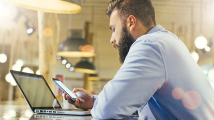 View from the side,young bearded businessman in blue shirt sits at table in cafe and use smartphone, laptop in front of him.Entrepreneur working outside office. Man surfing Internet on digital gadget.