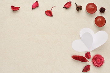 romantic background - rose petals, two paper hearts and candles. Happy valentines day
