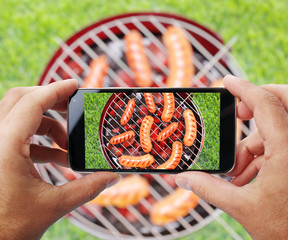 Taking photo of grilling sausages by smartphone.