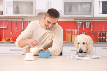 Man and  dog enjoying breakfast at the kitchen