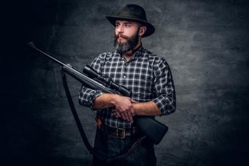 A hunter holds a rifle.