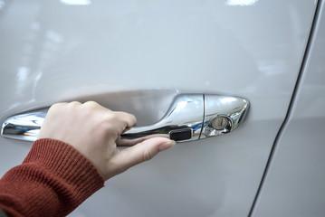 Girl hand holding car doorhandle