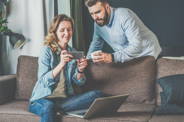 Young bearded man and woman sitting at home on couch and looking at laptop screen in hands of men. Girl holding smartphone. Couple shopping online, surfing internet.