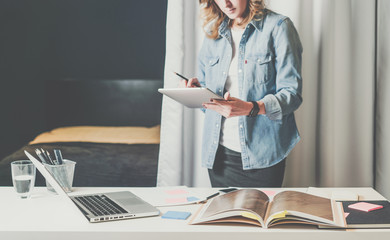 Office design studio, young businesswoman in denim shirt standing near desktop and leafing through catalog.On table is laptop,digital tablet. Girl chooses finishing materials for advertising catalogs.