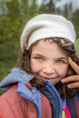 Outdoor portrait of cute smiling young girl with gap teeth.