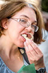 Portrait of woman in glasses  taking a bite and eating pastry outdoors.