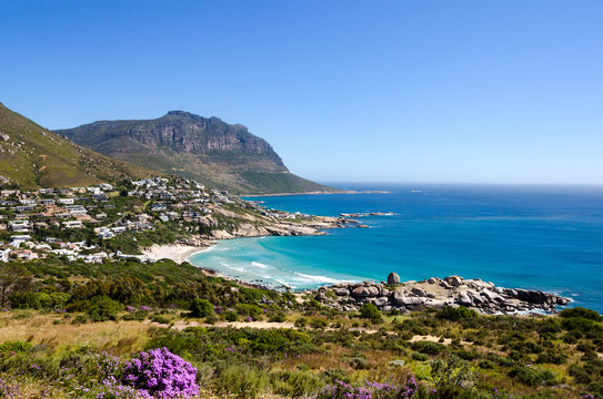 Coastline of Camps Bay near Cape Town in South Africa on a beautiful summer day with quite ocean and blue sky extending to the horizon. Beautiful vegetation beach and homes right of the coast