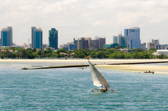 Coastline of Dar Es Salaam. A fishing boat is sailing along the beach towards the huge drainage pipe extending in to the ocean. The skyline with skyscrapers is in the background