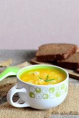 Chicken rice soup with potatoes, green onions and carrots in a bowl. Bread slices, burlap textile, spoon on wooden table. Homemade soup recipe. Vertical photo. Closeup
