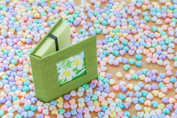 Green notebook and flower on cover with colorful pastel heart sh