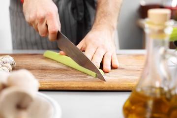 Krojenie warzyw. Kucharz sieka warzywa na desce do krojenia.