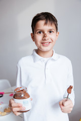 Cheerful little boy eating chocolate spread from jar by spoon