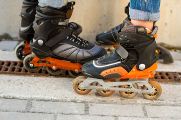 Legs in rollerblades. Inline skates and asphalt. Durable materials and new design.