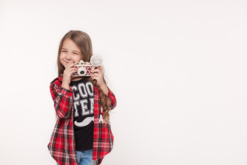 Beautiful smiling child girl holding a instant camera