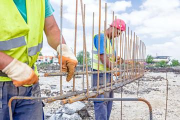 Construction worker binding rebar for reinforce concrete column
