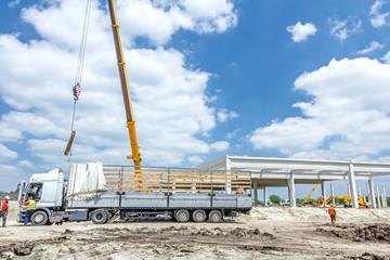 Mobile crane is unloading concrete joist from truck trailer