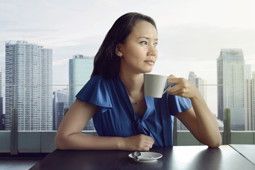 Attractive asian woman enjoying relaxing time while drinking coffee