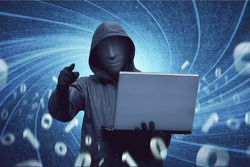 Hacker man with anonymous mask holding laptop
