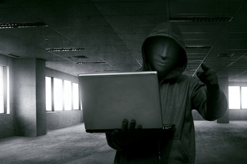 Hacker man with anonymous mask holding laptop while standing