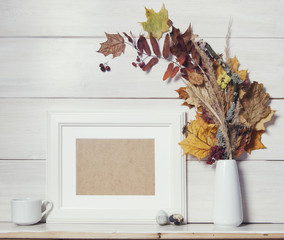 Autumn background template with white wooden frame and dry leaves