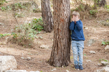 Little Caucasian boy closing his face with hands as if playing hide and seek or scared of something.