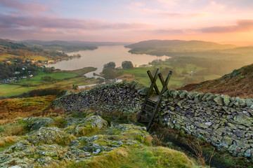 Beautiful sunset over Windermere in the Lake District with a stile and stone wall in the foreground. Wall mural