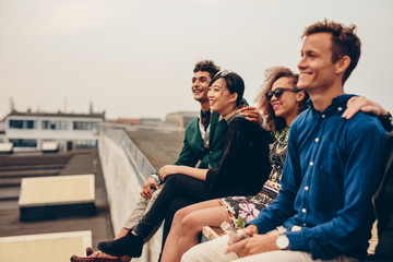 Friends sitting together on rooftop Wall mural