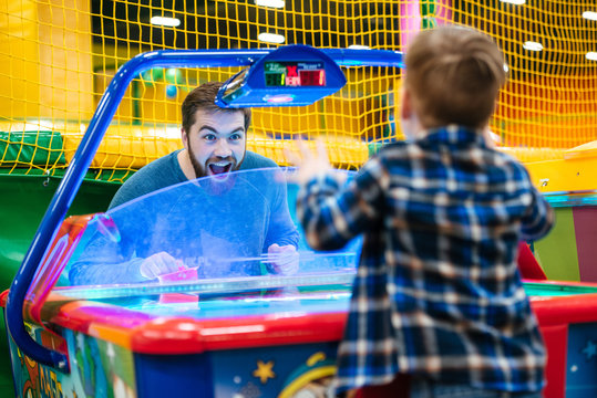 Father and son playing air hockey game at amusement park