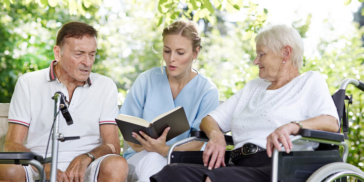 Carer reads a book to the elderly persons