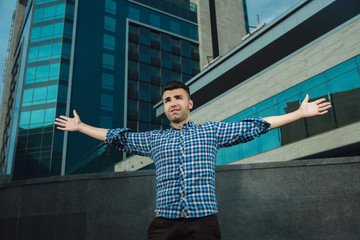 young man in a plaid shirt and shorts, spreads his arms to the side as the in-flight, in the background of the building. Low angle, wide angle