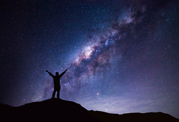 Milky Way landscape. Silhouette of Happy man standing on top of