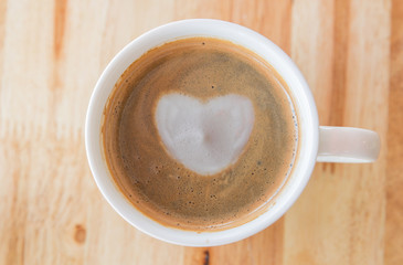 Heart in cup of coffee with in a white cup on wooden background.