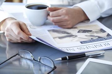 Businesswoman reading newspaper on worktable