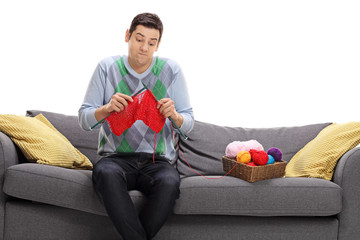 Confused guy sitting on a sofa and attempting to knit
