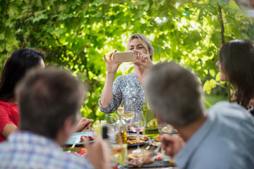 A woman takes a picture of her friends lunching on a terrace