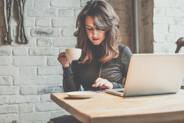 Young woman sitting in coffee shop at wooden table, drinking coffee and using smartphone.On table is laptop. Girl browsing internet, chatting, blogging. Female using phone, reading message.