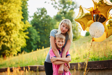 Mother and her little son with gold balloons in summer day. Happy family mom and kid hugging