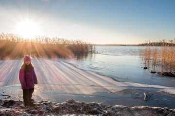 Young girl standing at a shore looking at winter sunset with sun flares on the snow and ice.
